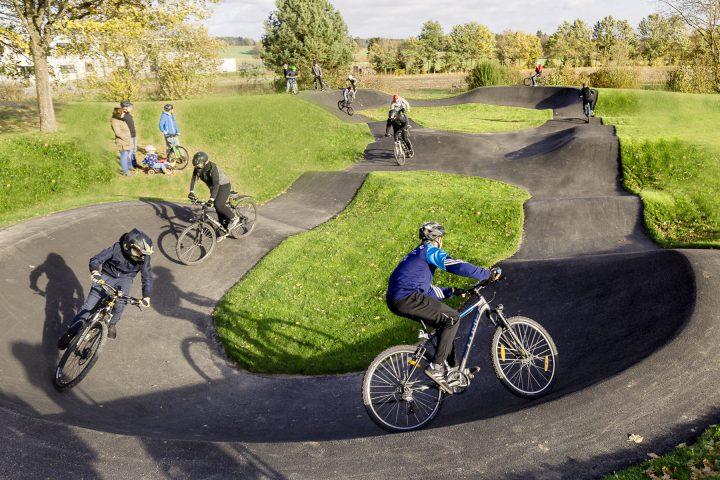 Pumptrack im Grünen mit Radfahrern und Zuschauern. Ein Pumptrack ist eine speziell geschaffene Mountainbikestrecke im Rundkurs.