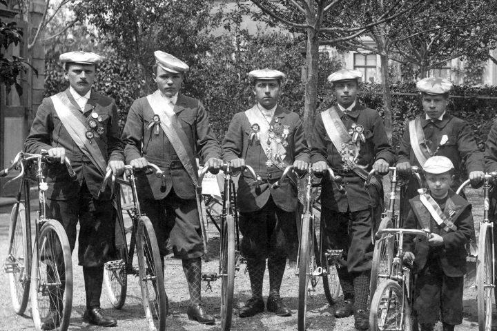 Historisches Foto einer Gruppe von Fahrradfahrern, 8 Männer, ein Kind. Festliche Uniformen mit Schärpe.