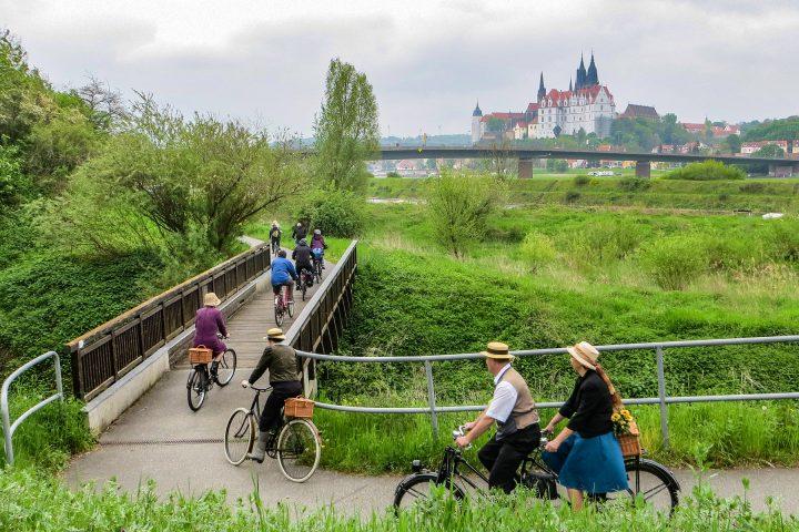 Von hinten zu sehende Radfahrer auf dem Elberadweg. Sie fahren über eine kleine Brücke inmitten von Wiesen und Büschen. Im Hintergrund die Elbe und Schloss Meißen.