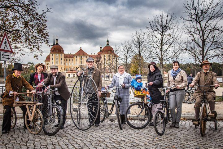 Vor dem Schloss Moritzburg sind in einer Reihe neun Frauen, Männer und Kinder mit ihren historischen Fahrrädern aufgereiht. Manche Personen tragen sogar historische Kleidung.