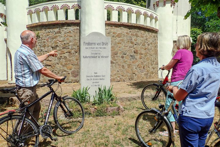 Zwei Frauen und ein Mann stehen mit ihren Fahrrädern vor dem »Draisstein«, einem Denkmal für den Erfinder Karl von Drais. Der Stein wurde 1912 aufgestellt und befindet sich unterhalb des Friedensturms Weinböhla.
