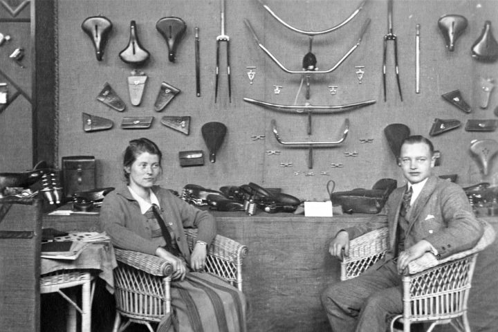 Zwei Firmenvertreter in guter Kleidung sitzen auf Stühlen vor einer Präsentationswand mit Fahrradteilen.