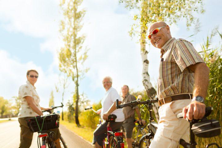 Ländliche Allee mit einem Maisfeld. Mehrere Senioren mit Fahrrädern sind startbereit und blicken auf den Fotografen zurück.